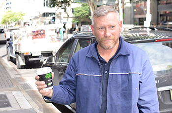 man holding UBET advertised coffee cup